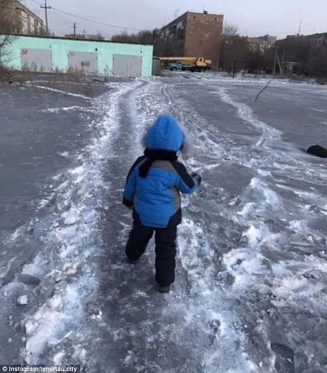 Một em bé đang đi trên con đường phủ đầy tuyết đen.