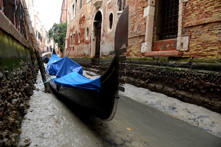 Thuyền nằm trơ trọi trên lớp bùn ẩm ở đáy kênh đào Venice.