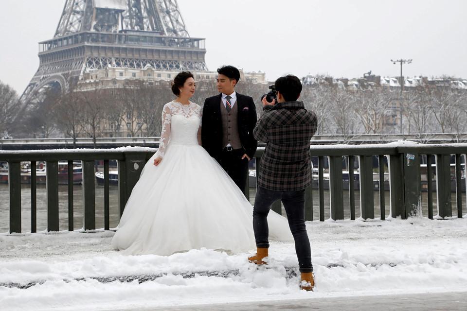 Một cặp đôi chụp ảnh cưới trên cầu Bir-Hakeim trong trời tuyết.