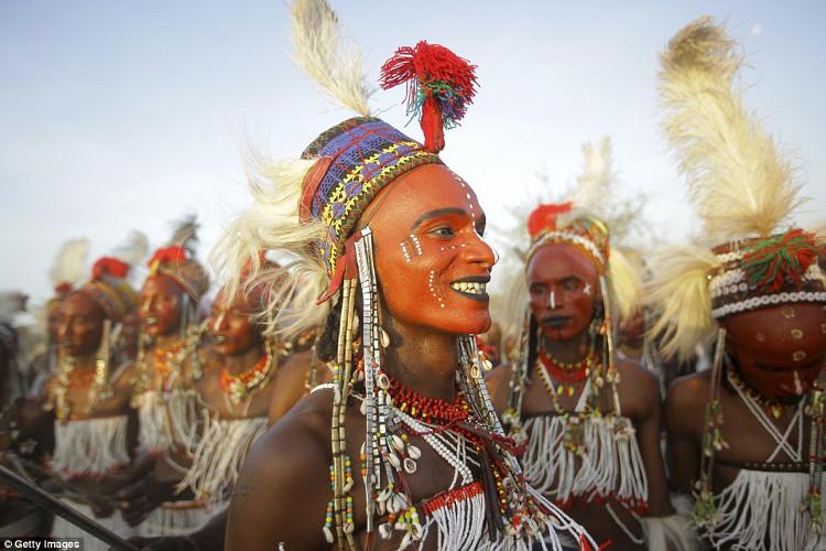 Đàn ông sơn đất sét đỏ lên mặt, kẻ mắt màu đen, tô son để khoe răng trong điệu nhảy Yaake.