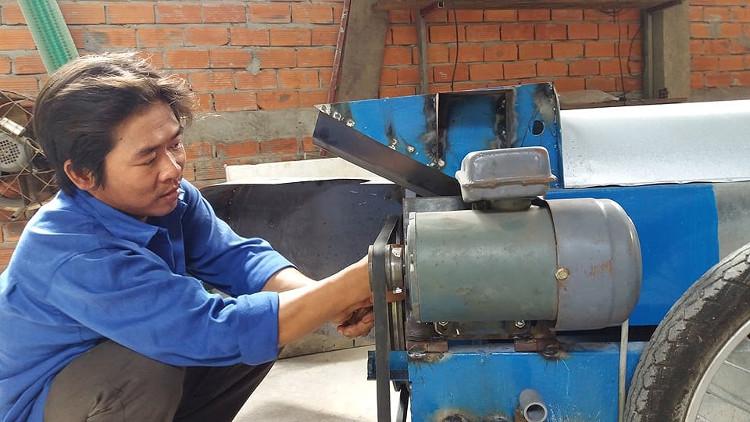 Anh Trần Huỳnh Long bên sản phẩm máy rửa trái hồng xiêm do mình sáng chế.