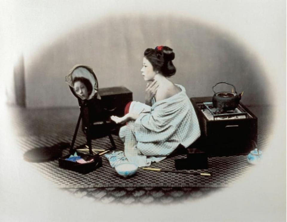 Một phụ nữ đang tô phấn trắng lên khuôn mặt và để lộ một bên vai trần.