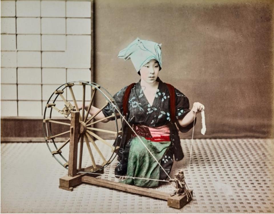 Một phụ nữ đang ngồi dệt vải.
