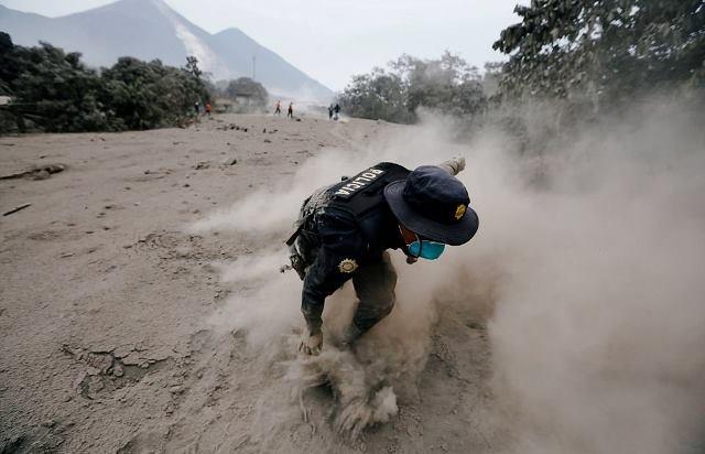 Một cảnh sát loạng choạng khi chạy khỏi nham tầng núi lửa Fuego.