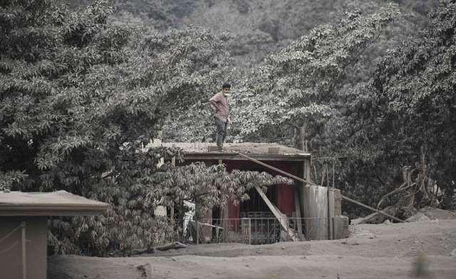 Một người đàn ông bần thần đứng trên mái nhà bao phủ tro núi lửa tại làng San Miguel Los Lotes ở tỉnh Escuintla.