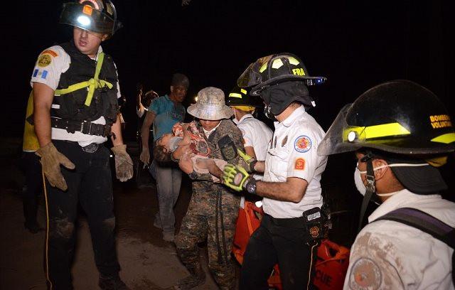 Các tình nguyện viên chuyển em nhỏ tới nơi an toàn.