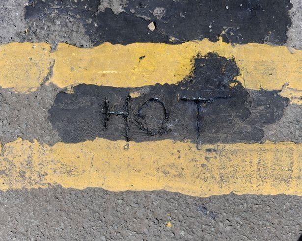 """Mặt đường nhựa ở phố Duke, thành phố Castlefield đã chảy ra đến mức người dân có thể viết chữ """"Hot"""" (Nóng) lên trên"""