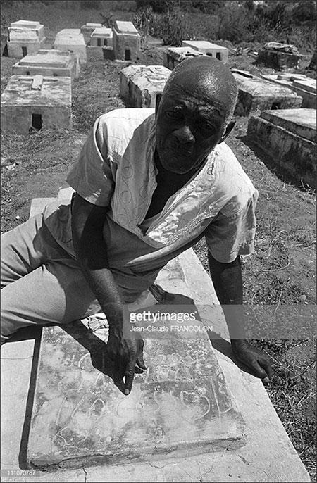 Ông Narcisse bên ngôi mộ của chính mình.