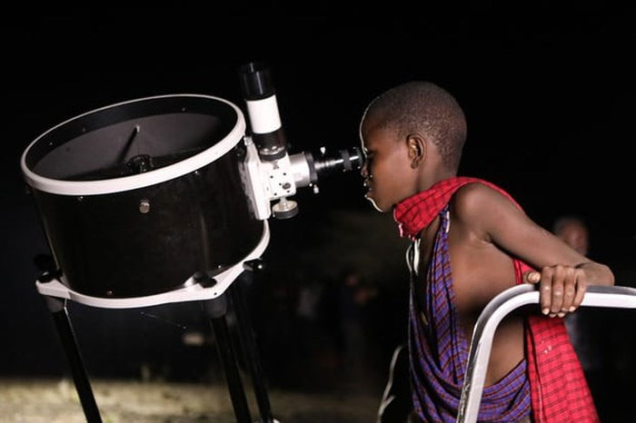 Một em bé Kenya xem trăng qua kính thiên văn