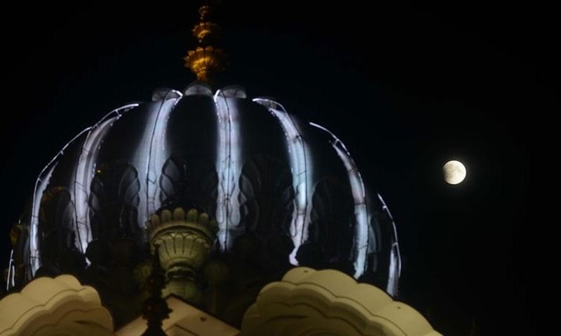 Đền Vàng nổi tiếng ở Amritsar, Ấn Độ, với Mặt Trăng rực sáng phía xa.