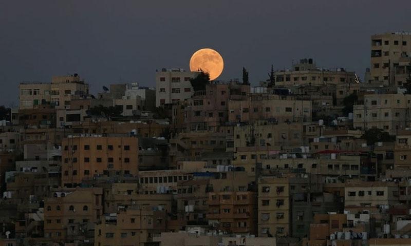 Mặt Trăng trông như đang nằm nghỉ trên những tòa nhà của thủ đô Amman, Jordan.