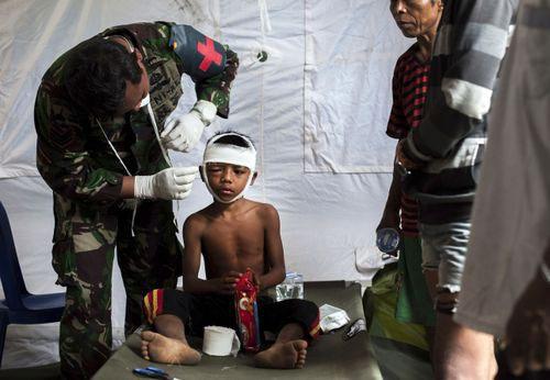 Một đứa trẻ được nhân viên y tế băng bó vết thương.