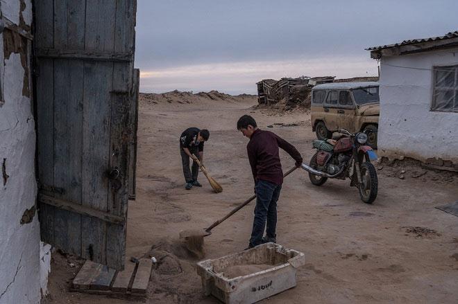 Người dân làng Akespe, Kazakhstan, dọn cát bị gió cuốn bao trùm khu vực mỗi ngày.