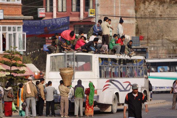Hành khách lên xuống xe buýt tại Nepal.