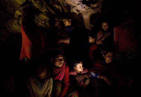 Một nhóm phụ nữ trẻ đang trò chuyện trước khi ngủ dưới một vỉa đá.