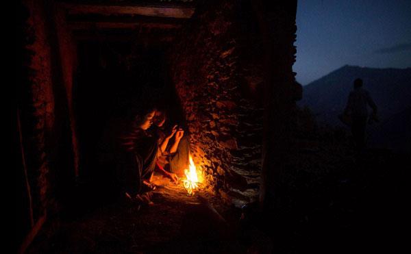 Nabina (17 tuổi) cùng Khadi (14 tuổi) đang co ro sưởi ấm bên ngọn lửa trong căn hầm của gia đình.