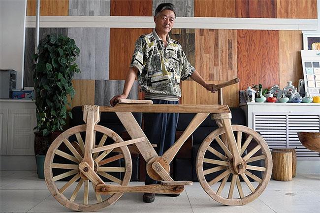 Ông He Yong bên chiếc xe đạp gỗ.