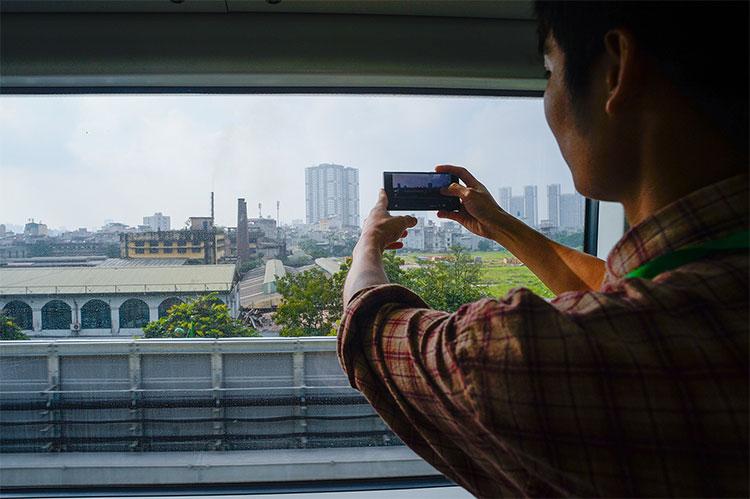 Nhiều người thích thú chụp ảnh cảnh Hà Nội từ bên trong toa tàu.