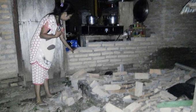Một người dân chỉ vào bức tường gạch đổ nát trong nhà tại làng Tobadak ở Trung Mamuju, phía tây tỉnh Sulawesi