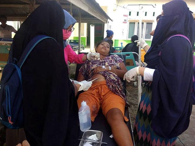 Nhân viên y tế điều trị cho một nạn nhân sống sót sau trận động đất ở ngoài bệnh viện tại Donggala,