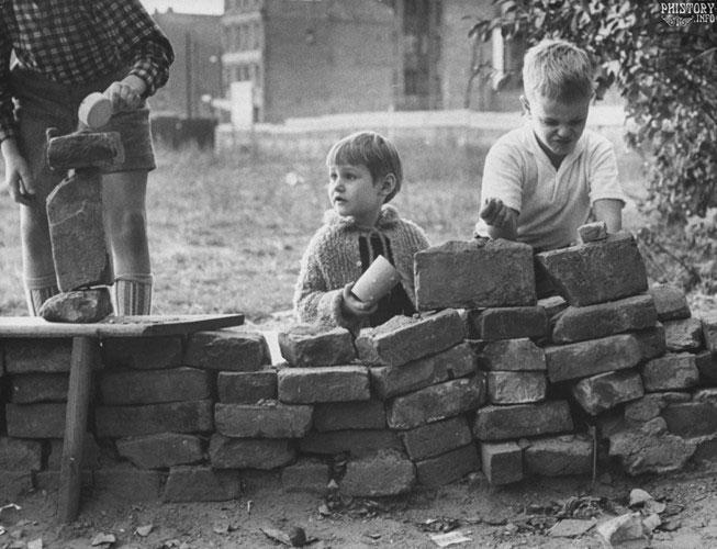 Những bé trai người Đức nghịch ngợm, đóng giả việc xây một bức tường năm 1961.