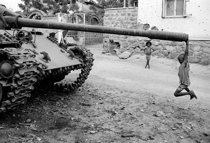 Một cậu bé ở châu Phi chơi đùa bên cỗ xe tăng bị bỏ hoang năm 1991.