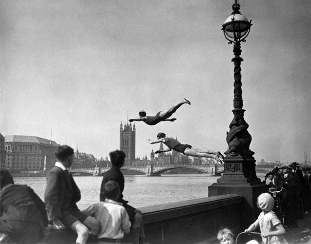 Nhiều người dân đứng trên cầu theo dõi các thợ lặn làm việc ở sông Thames năm 1934.