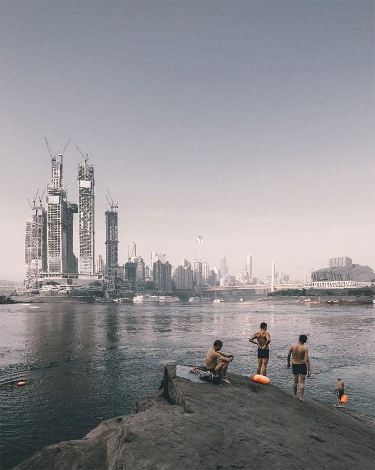 Những người đang bơi lội trên sông, bên kia bờ sông là công trình xây dựng Raffles City Chongqing