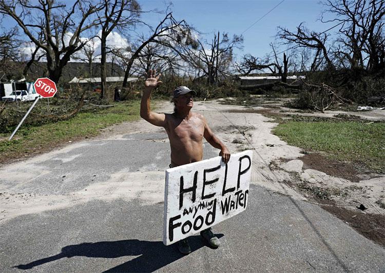 """Người đàn ông giơ biển """"Cần trợ giúp tất cả mọi thứ, thức ăn, nước uống""""."""