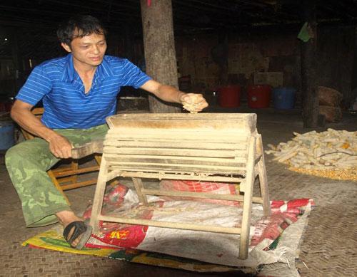 Anh Vương Hùng Nam bên chiếc máy bóc lạc quay tay bằng gỗ.