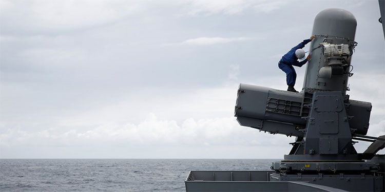 Một thủy thủ làm vệ sinh bệ phóng tên lửa trên tàu sân bay trực thăng Kaga.