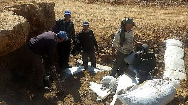 Nhóm khảo cổ đang thu thập những mảnh hài cốt trong hố chôn tập thể