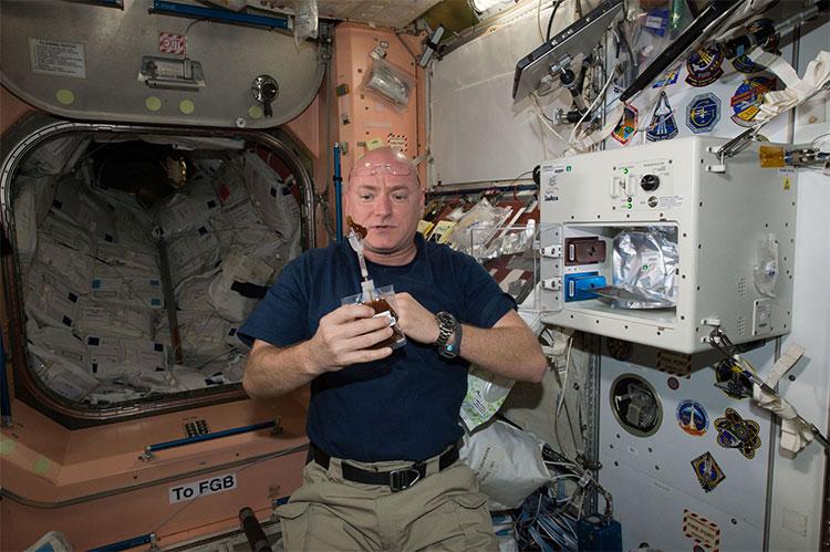Trong ảnh, phi hành gia Scott Kelly pha cà phê từ máy ISSpresso, trong khi cà phê bên trong cốc của ông trôi bồng bềnh.