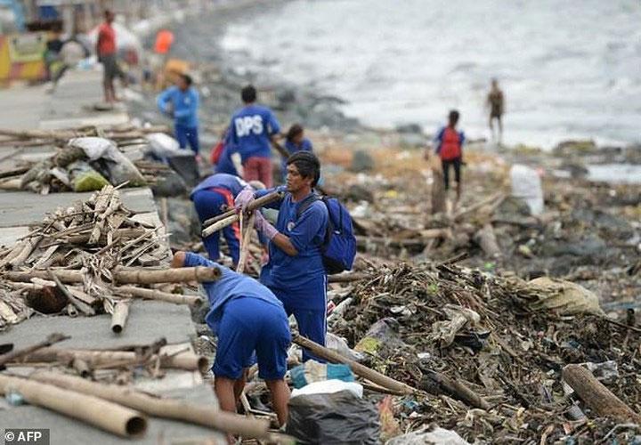 Các công nhận dọn dẹp đống đổ nát và rác rưởi bị Siêu bão Yutu cuốn vào bờ biển Philippines ngày 30/10.