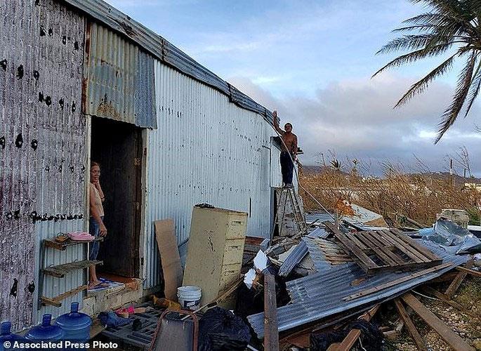 Một người đàn ông đang sửa lại căn nhà bị Yutu phá hỏng khi siêu bão này đổ bộ vào Saipan