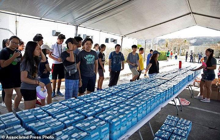 Các tình nguyện viên phát nước và nhu yếu phẩm cho người dân vùng chịu ảnh hưởng của bão.