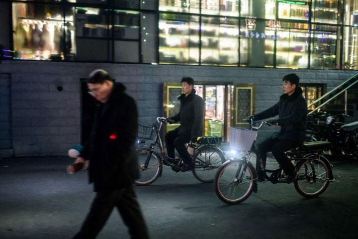 Hai người đàn ông đạp xe qua một con phố ở Sinuiju.