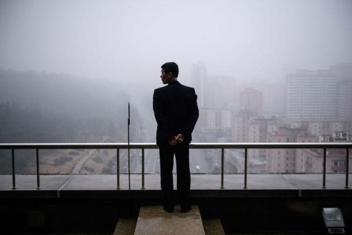 Một người đàn ông đứng trên tầng cao nhất của Khải Hoàn Môn, quan sát khung cảnh Bình Nhưỡng.