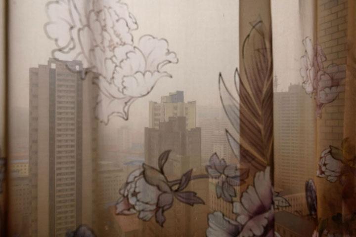 Quang cảnh thủ đô Bình Nhưỡng từ trên cao nhìn qua tấm rèm của khách sạn Koryo.