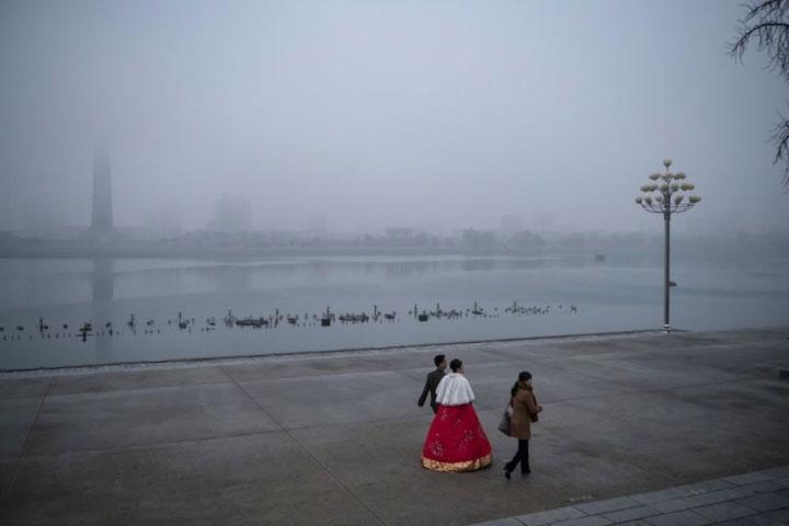 Cặp cô dâu, chú rể đi bộ ven bờ sông Teadong trong một buổi chiều sương giá, phía xa xa là tháp Jechu.
