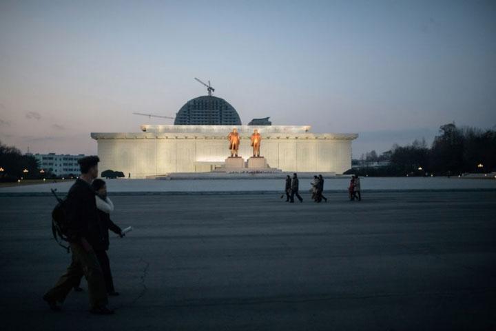 Người đi bộ đi ngang qua các bức tượng của cố lãnh đạo Triều Tiên Kim Il Sung (Kim Nhật Thành) và Kim Jong Il tại thành phố biên giới Sinuiju.