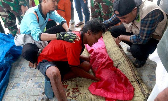 Trong ảnh, một người cha đang than khóc bên thi thể đứa con thiệt mạng trong sóng thần ở Nam Lampung.