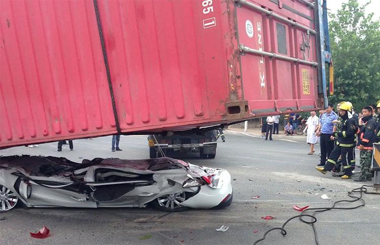 Một xe đầu kéo bị lật làm rơi container đè bẹp dúm chiếc ôtô con bên cạnh ở Thanh Đảo, Trung Quốc