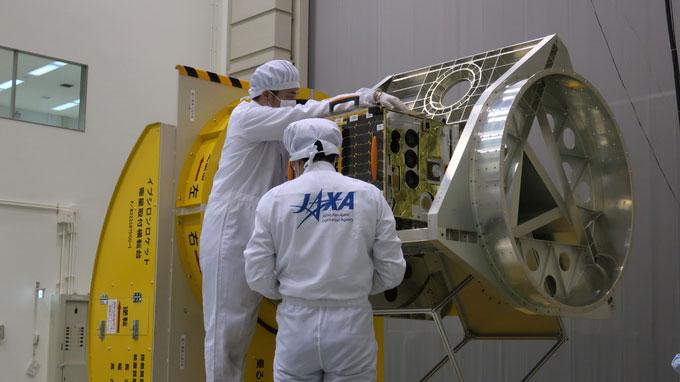 Các kỹ sư JAXA đang lắp đặt thử nghiệm vệ tinh vào bộ gá đặt trong tên lửa.