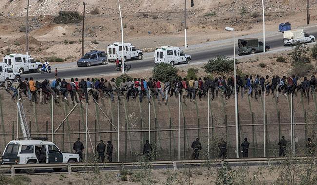 Cảnh sát dân sự (Guardia) Tây Ban Nha theo dõi những người nhập cư từ châu Phi ngồi trên hàng rào biên giới