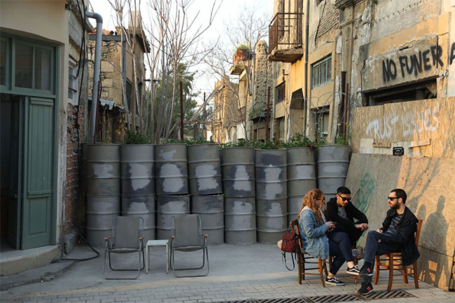 Một số người ngồi uống cà phê bên cạnh ranh giới được gia cố ở vùng đệm phía nam thuộc Hy Lạp