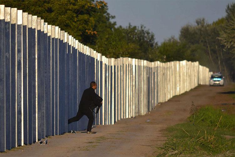Một người di cư bỏ chạy sau khi xâm nhập vào Hungary bằng cách vượt qua hàng rào bảo vệ tạm thời