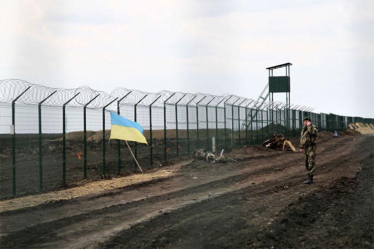 Một sĩ quan bảo vệ biên giới Ukraine nói chuyện qua điện thoại cạnh hàng rào ở biên giới Ukraine - Nga