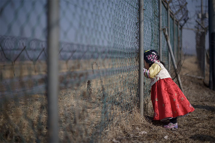 Một bé gái nhìn qua hàng rào quân sự hướng về phía Triều Tiên tại công viên Imjingak