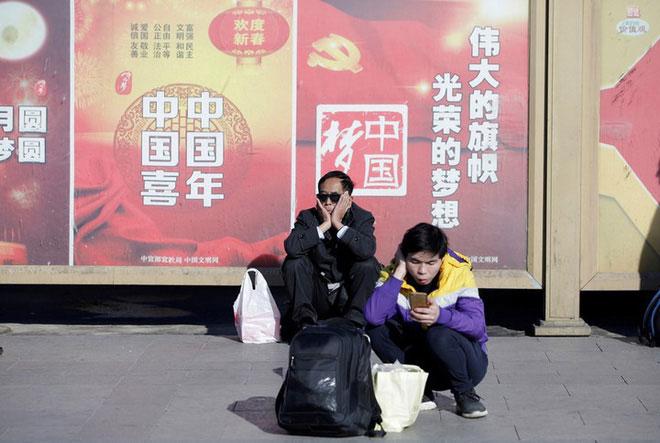 Hành khách ngồi chờ bên ngoài nhà ga Bắc Kinh